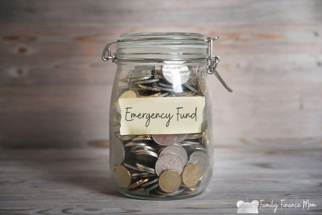 Coins in glass money jar with savings label, financial concept. Vintage wooden background with dramatic light.