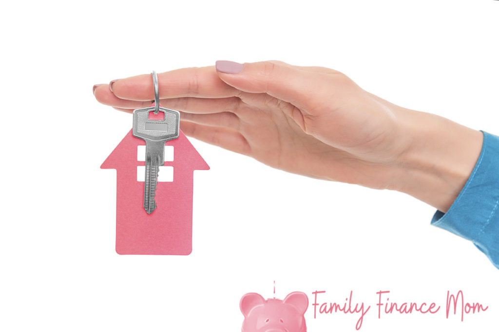 Key from the house in a female hand. Isolated on white background.