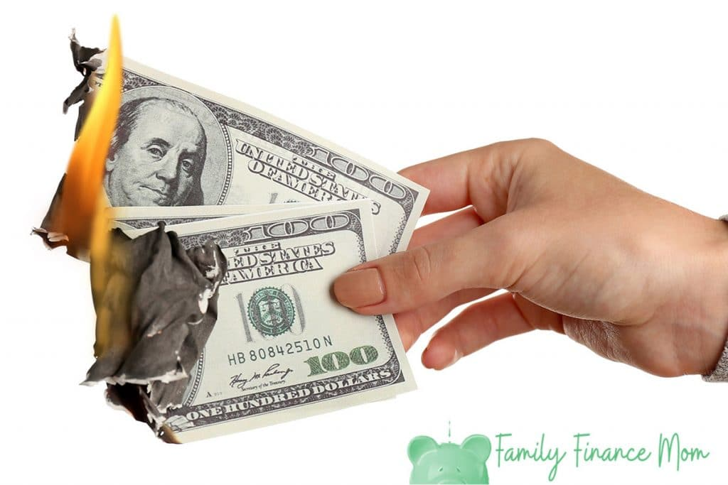 Woman burning dollar banknotes isolated on white