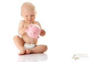 Young baby boy playing with pink piggy bank isolated